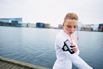 Female Jogger Monitor Her Progress On Smartphone